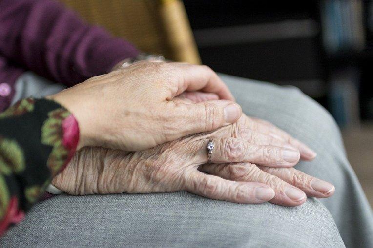 Foto på en äldre människas händer i knäet