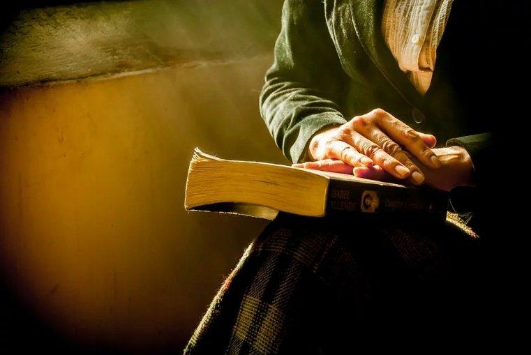 Foto på en äldre människa med en bok i knäet