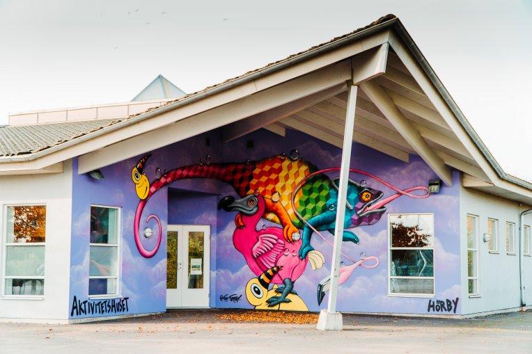 Foto: Graffitimålning på Aktivitetshusets fasad som föreställer olika fantasi djur